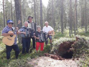 5 personer med gitarr, dragspel och ukulele som står bland blåbärsris i en tallskog